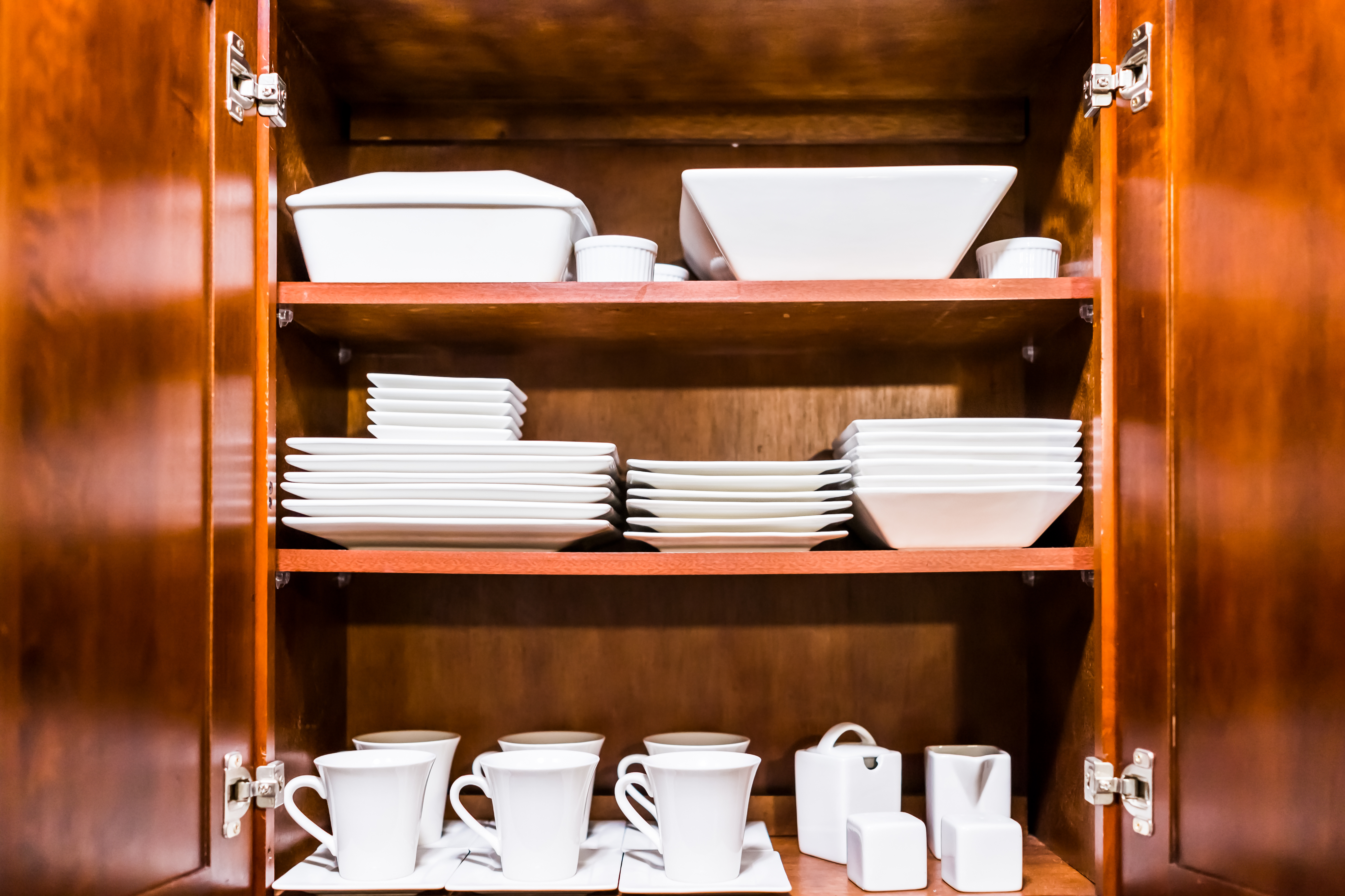 Open wooden kitchen cabinet door cupboard with many white dishes, plates, cups on shelves closeup